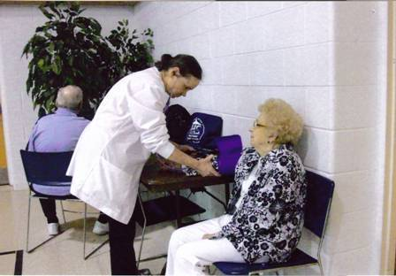 Nurse taking blood pressure at STA-50 meeting