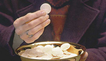 Eucharistic minister holding host in right hand