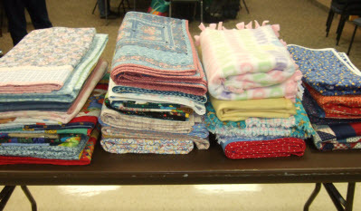 Quilts piled on table