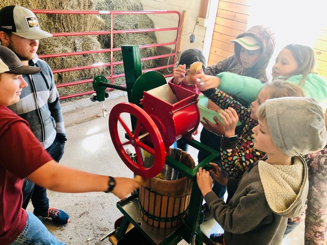 Some of our School of the Holy Family Students helping our younger students make Apple Cider at the Apple Creek Farm