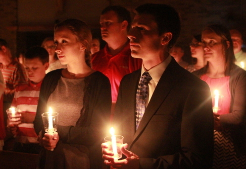 Young Alumni holding lit candles at Easter Vigil