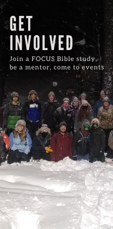 Students in the snow in the dark after snowshoeing.