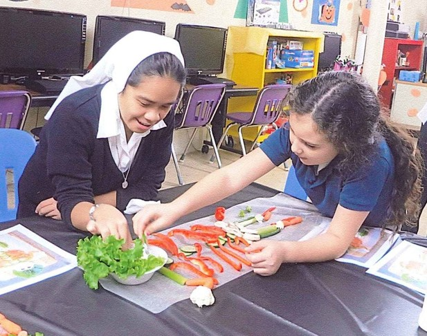 A Novice of the Sisters of Christian Charity arranges some vegetable art with a student at the Learning Center