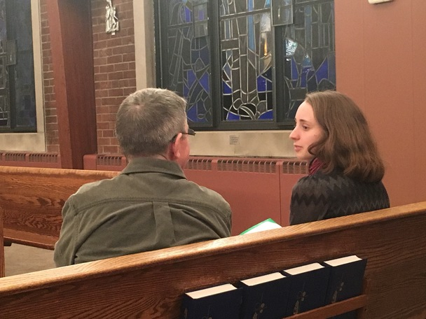 A non-student and student parishioner meet in the chapel for conversation.