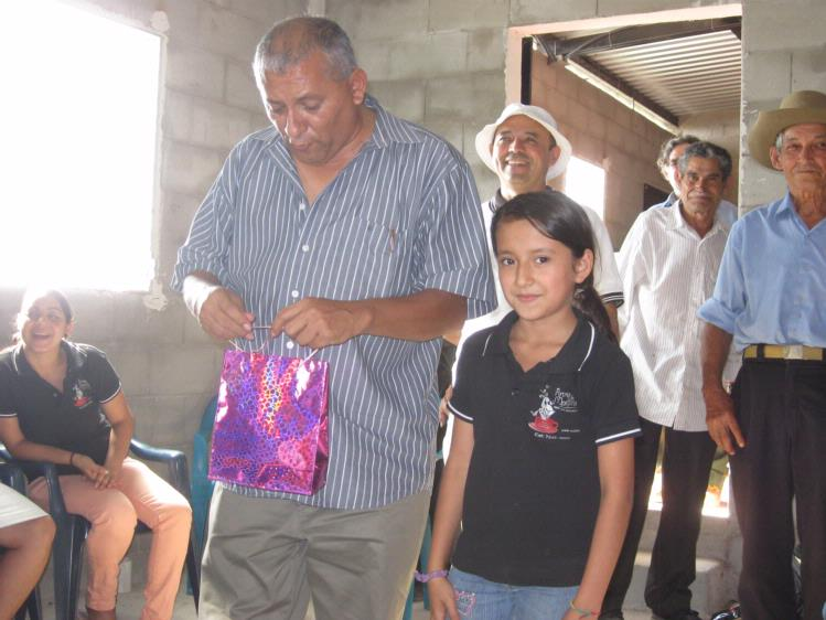 Padre Rafael and Blancavictoria present Kayla with a gift.