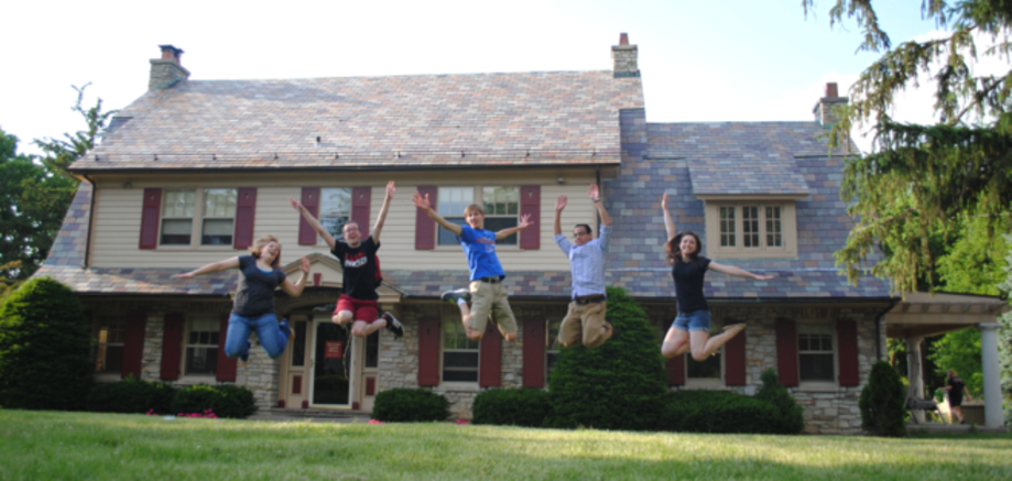 Students jumping in front of the Newman Center house