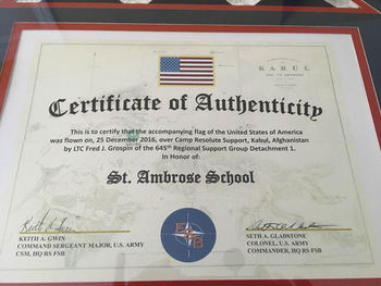 Parent presents flag flown in Afghanistan to St. Ambrose School