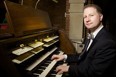 Organist Johann Vexo seated at the Kilgen Pipe Organ at Our Lady of Refuge in Brooklyn