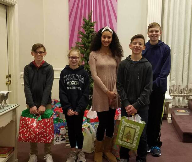 7th graders holding gifts in front of tree