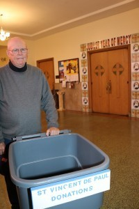 Albert Pierce places a collection bin outside the Holy Door at St. Joseph Parish in Fitchburg.
