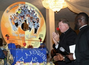 Bishop McManus applauds after unveiling the replica of the CD with help from Father Eric K. Asante. Photo by Tanya Connor
