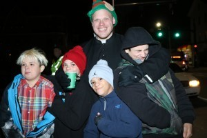 Tanya Connor | CFP Father Jonathan J. Slavinskas, administrator of Our Lady of Providence Parish at St. Bernard's Church, lights up a dark Lincoln Street with his smile as he shares hot chocolate and laughs with Joseph Rouleau, Shane Wilkins, Shace Wilkins and Stephen Rouleau.