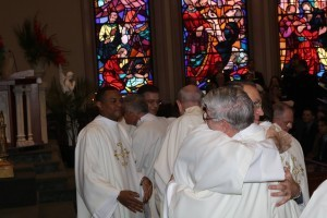 Newly ordained Deacons Paul Covino, background, and  Stephen Kohut is embraced by priests of the diocese.