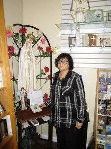 Patricia Quintiliani shows the shrine to Our Lady of Fatima that is in A Shower of Roses store in West Boylston. Photo by William T. Clew