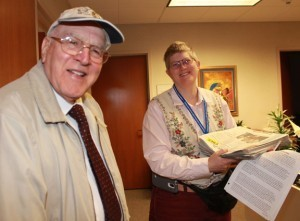 Louy Tripodi delivers papers to Charlotte Lehmann at the Pastoral Care office of St. Vincent Hospital. Photo by Tanya Connor