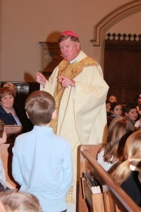 Photos by Tanya Connor Bishop McManus quizzes the younger generation at Catholic Schools Week Mass Monday for Our Lady of the Valley Elementary School in Uxbridge. He celebrated Mass in St. Mary's Church.