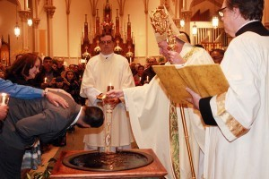 Bishop McManus baptizes Joseph Paradis. / Photo by Tanya Connor