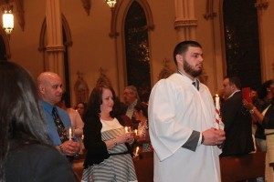 Joseph Paradis and his godparents, Tony and Yolanda Torres, join a procession of the newly baptized during the Easter Vigil at St. Paul Cathedral. /Photo by Tanya Connor