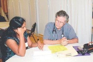 Dr. John Howland, new medical director of St. Anne's Free Medical Program in Shrewsbury, consults with Dr. Kanchana Myneedu, an observer, during program hours.