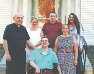 Posing for a family photo with Father Ryan, in the back row are, left to right, Ryan Lauria, Michael John Lauria and Colleen Lauria.  In the front row are John Lauria and Mary Lauria.