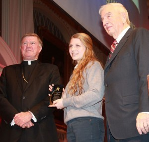 Holy Name senior Kaitlyn Roberts, flanked by Bishop McManus and steering committee chairman Robert R. Pape, displays her Paul & Dorothy Kervick Award for Leadership at the Adopt-A-Student Recognition Dinner Monday at Mechanics Hall.  Photo by Tanya Connor