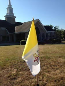 Vatican flags line the lawn outside St. Joseph Parish in Charlton.