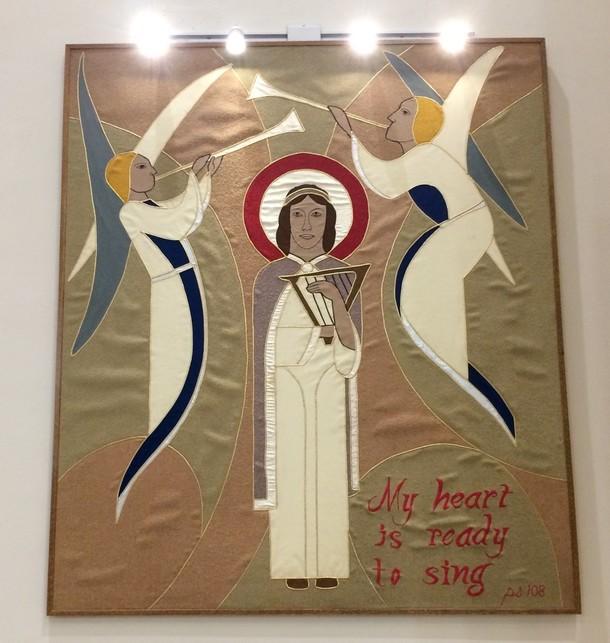 The St. Cecilia tapestry was installed in the renovated choir area in 1986. CTK committee member and head of Aia Architects (Greenfield, MA), Pierre A. Belhumeur, lead the renovation project and worked to approve the tapestry.