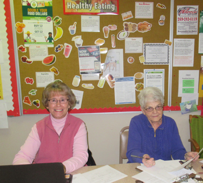 Judy and Cathy checking clients in