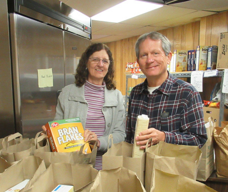 Dave and Deb are filling grocery bags to give to clients