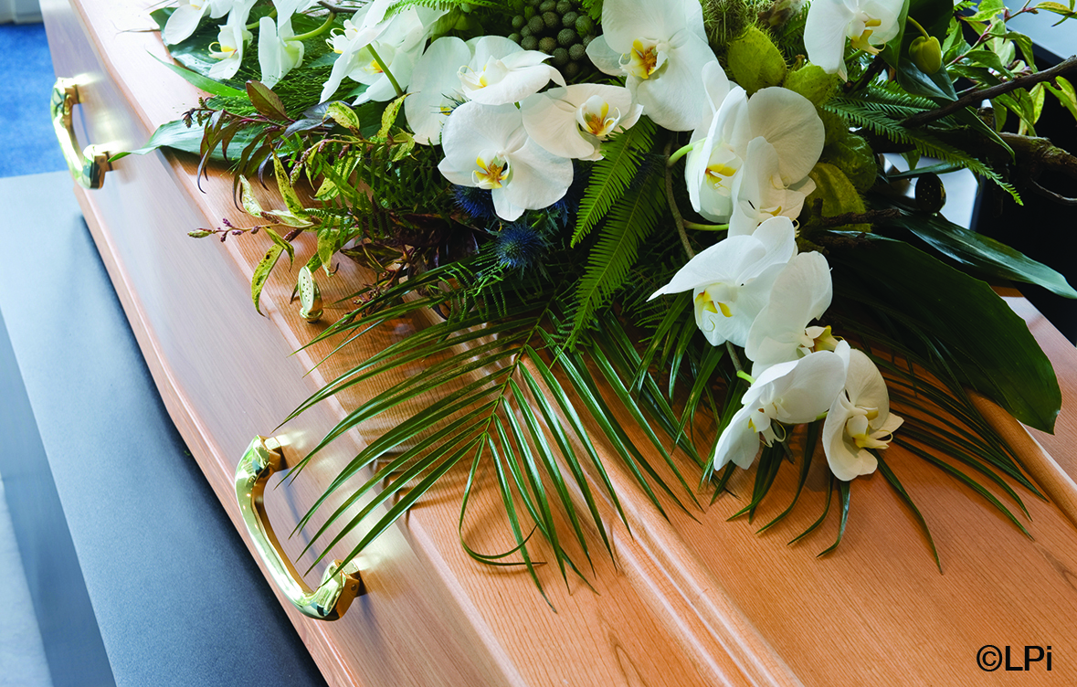 Flower arrangement, white and green, sitting on top of a wood casket.