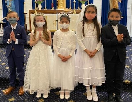 Children in white dresses and suits for First Holy Communion
