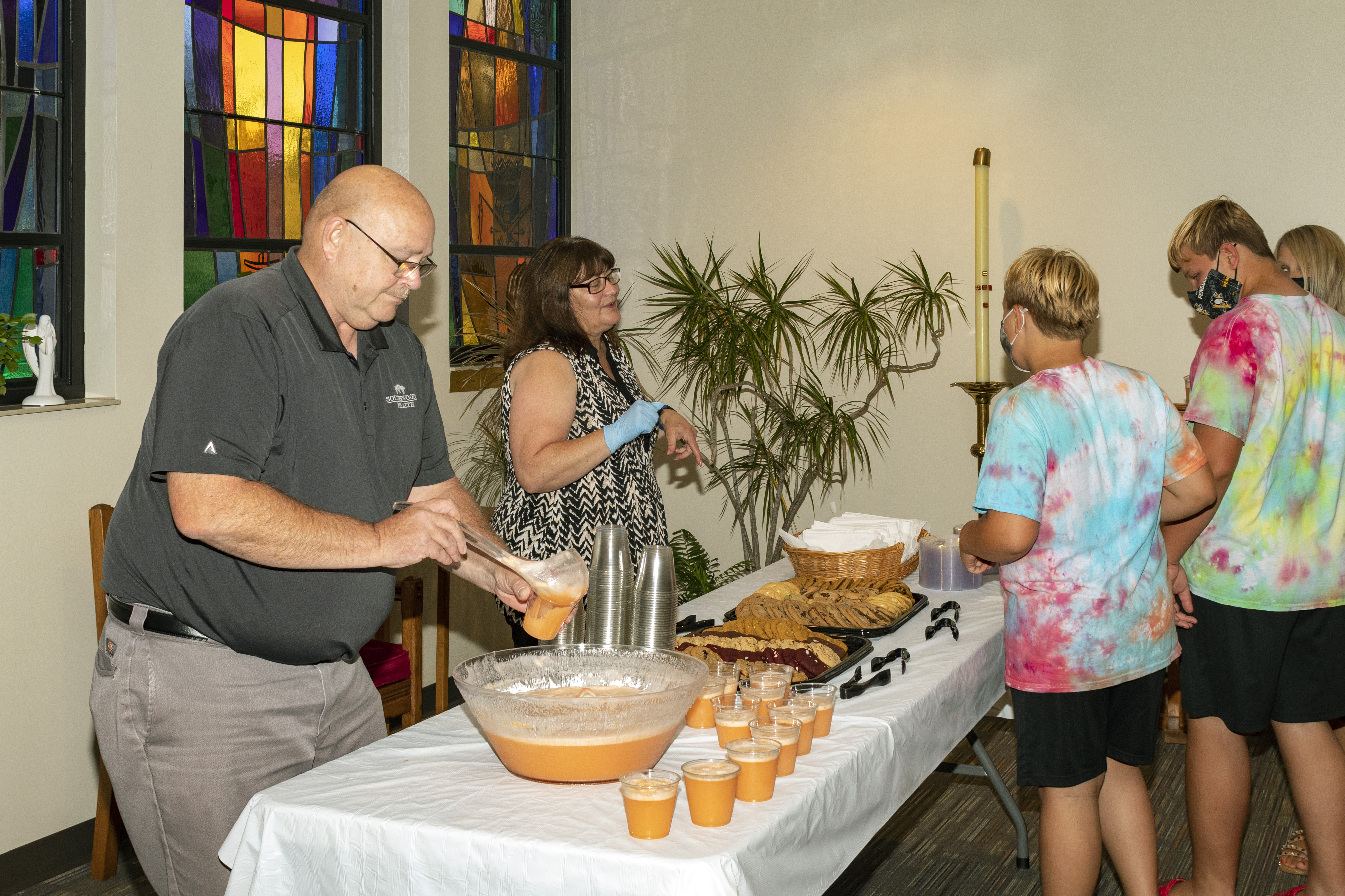 St. Thomas Director of Religious Education Mrs. Virginia Crum and husband Dennis treat students to snacks after mass on Catechetical Sunday..