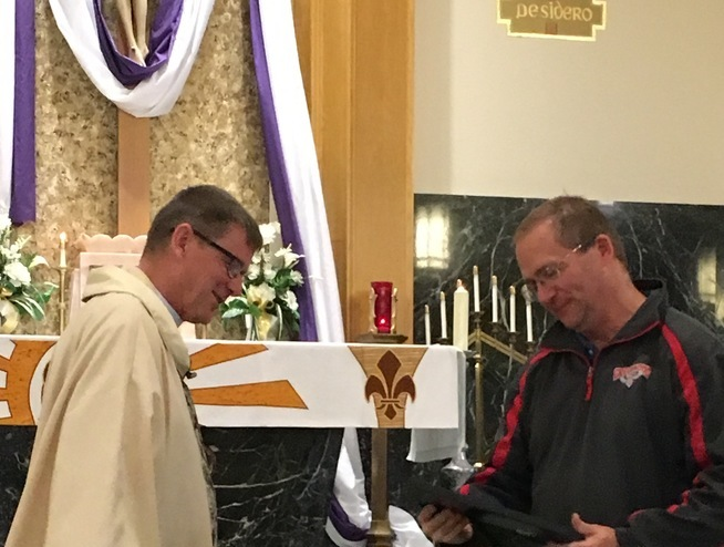 Fr. John Fortune Pastor of St. Francis in Saikeri, Kenya gives signed Sister Parish Covenant Agreement to Parish Council president Dean Lindner.