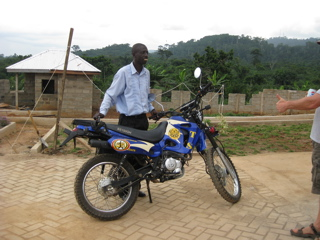Augustin Prinicpal at Awaso Village school at Casa Maria courtyard with his motorcyle.
