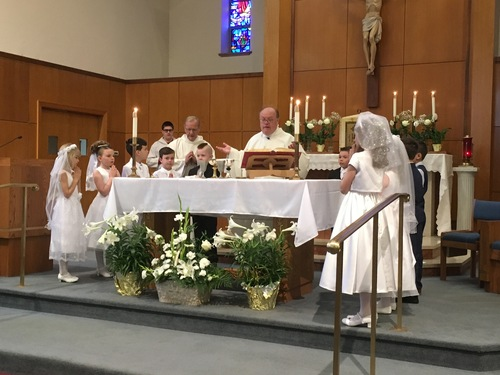 First Communion Kids around Alter with Fr. Wally Keymont