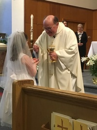 Fr. Wally Keymont giving little girl First Holy Communion