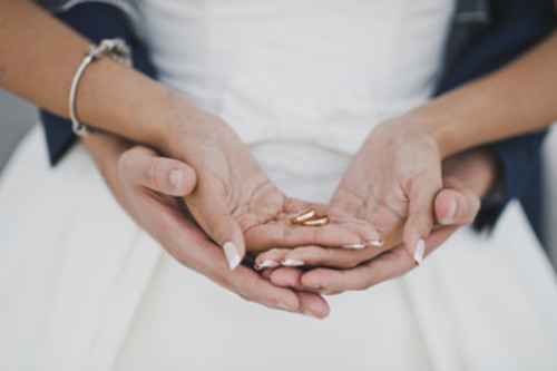 A pair of hands holding another pair of hands with wedding rings.