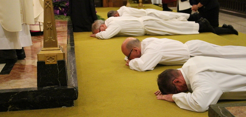 Deacons lie prostrate before the altar.