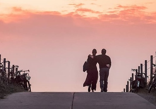 A woman and a man walking over a bridge