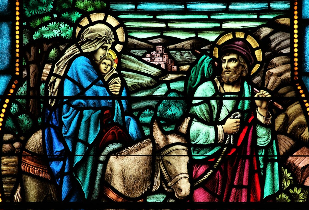 Stained glass image of Mary holding Baby Jesus, riding the donkey guided by St. Joseph.