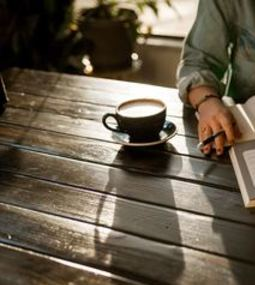 Picture of person reading book with coffee cup