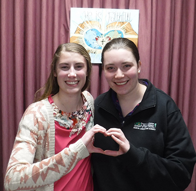 Two young ladies forming a heart with their hands