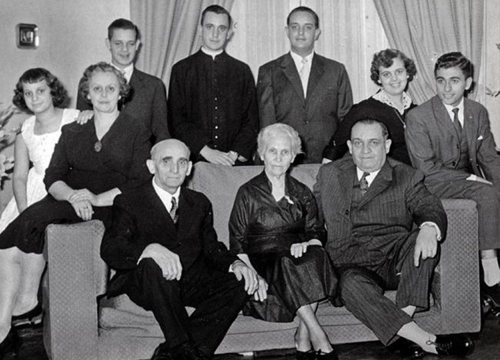 10 members of the Bergoglio family: adult children standing behind couch, parents and grandparents seated on couch