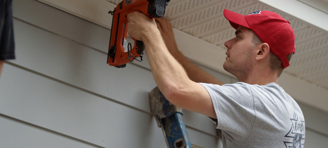 Man fixing soffit on house