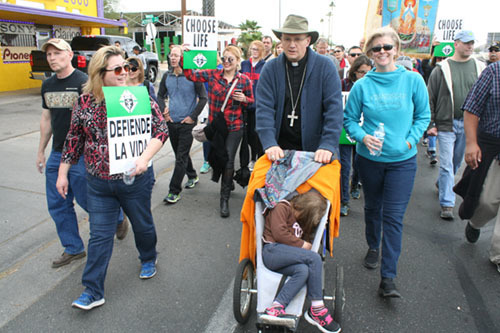Bishop Edward J. Weisenburger walks with Shannon Federoff, right, as he pushes a stroller occupied by her grand-daughter, Lilly, 4, during the March for Life in Tucson Jan. 20.