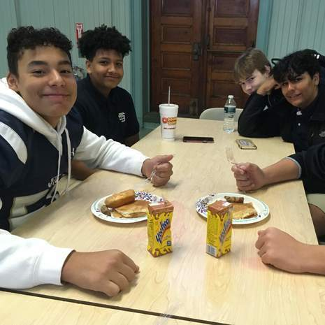 Four happy high school boys at lunch at St. Bernard's High School.