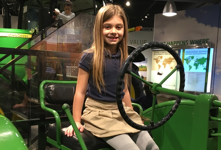 Student on tractor at the John Deere Museum