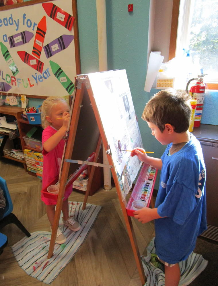 preschool students painting at easel