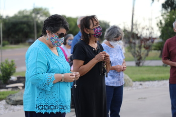 Parishioners pray the rosary for those affected by COVID