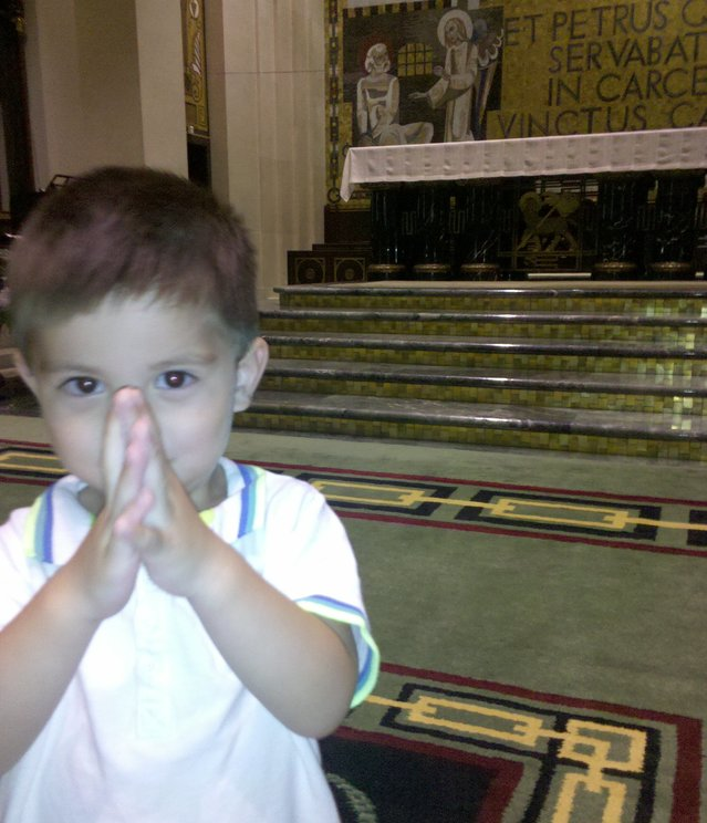 Little Boy praying and looking directly towards the viewer